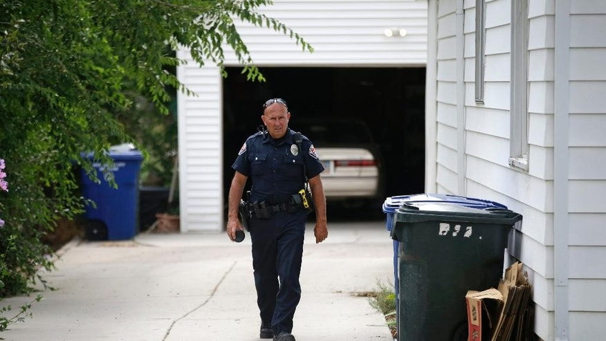 A police officer walks on a driveway is during an investigation after a 12-year-old girl was found dead Friday, July 17, 2015, in West Valley City, Utah. (AP Photo/Rick Bowmer)