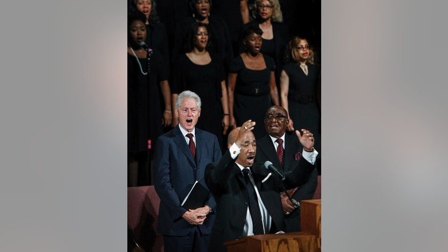 Former President Bill Clinton, left, sings a hymn during the funeral for Judge D'Army Bailey at the Mississippi Boulevard Christian Church, Saturday, July 18, 2015, in Memphis, Tenn. Bailey helped preserve the Memphis hotel where civil rights leader Martin Luther King Jr. was assassinated and turn it into the National Civil Rights Museum. (Mark Weber/The Commercial Appeal via AP) MANDATORY CREDIT