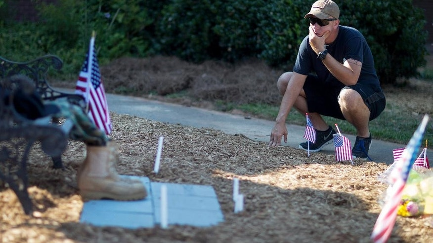"U.S. Army Pfc. Nolan Opp visits the memorial for his former classmate and JROTC cadet Skip Wells at Sprayberry High School where they both attended, Friday, July 17, 2015, in Marietta, Ga. Wells was one of four Marines killed in Thursday's shooting in Chattanooga. ""What I remember most is that fact that he never put himself before anybody else,"" said Opp. ""He had a huge future. It's just tragic that it ended this way."" (AP Photo/David Goldman)"