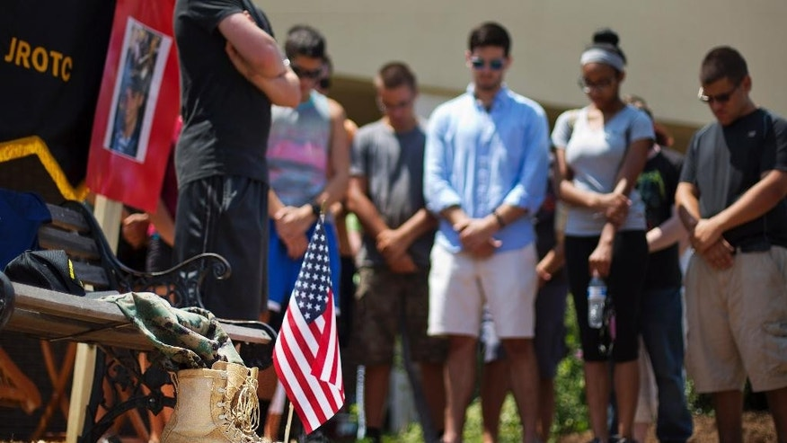 Boots sits next to an American flag as current and former JROTC students hold a moment of prayer at a memorial to Skip Wells at Sprayberry High School where Wells attended Friday, July 17, 2015, in Marietta, Ga. Wells was one of four Marines killed in Thursday's shooting in Chattanooga. (AP Photo/David Goldman)