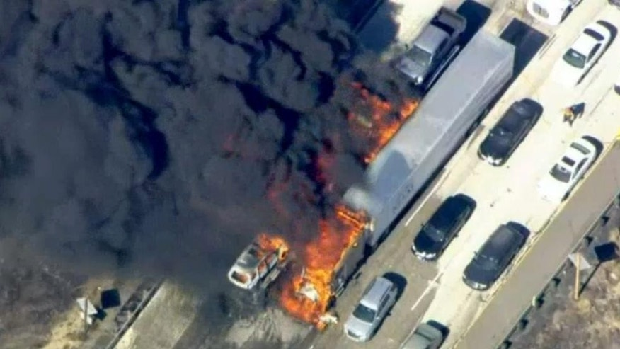In this frame from video provided by NBC4, smoke rises from vehicles as a fast-moving wildfire swept across a freeway Friday, July 17, 2015, near Hesperia, Calif. The fire swept by desert winds burned on both sides of Interstate 15, the main connector between Southern California and Las Vegas that was crowded with vehicles. (NBC4 via AP) MANDATORY CREDIT