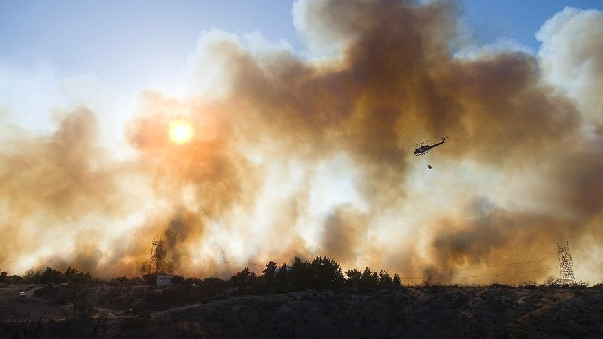 A helicopter prepares for a water drop over a fire near Oak Hills, Calif., Friday, July 17, 2015. The fire started in the Cajon Pass along Interstate 15, the main highway between Southern California and Las Vegas and quickly chewed through bone-dry brush. (James Quigg/The Victor Valley Daily Press via AP)