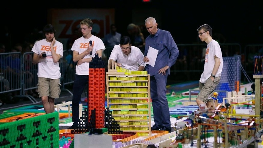 Judges look over parts of chain reaction machine as Zeal team members discuss the inner workings at the Michigan Science Center, Saturday, July 18, 2015 in Detroit. The team has failed to set a record for building the largest chain reaction machine. The machine activated Saturday included more than a half-million objects, but lead builder Steve Price says some sections failed, which meant there weren't enough completed steps to break the record. Organizers say the current Guinness World Records mark for a Rube Goldberg machine had 300 steps. Price says his machine had between 400 and 500 steps but the number likely fell below 200 with the sections that failed. (AP Photo/Carlos Osorio)
