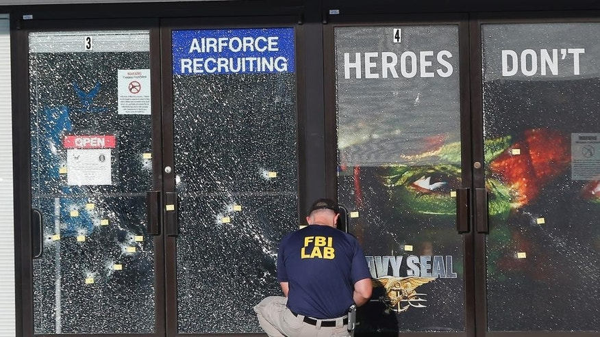 FILE - In this July 17, 2015 file photo, an FBI investigator investigates the scene of a shooting outside a military recruiting center in Chattanooga, Tenn. The deadly shootings of Marines at two Tennessee military sites illustrate the threat FBI officials in recent months have warned about: violence by a lone gunman with apparent terroristic aspirations against a vulnerable government target.  (AP Photo/John Bazemore, File)