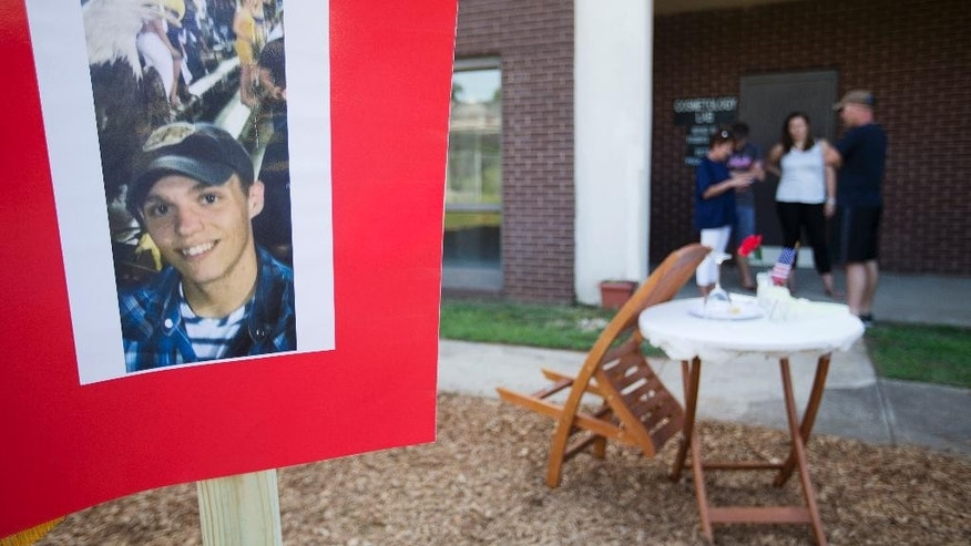 A photo of Skip Wells is posted next to a traditional fallen comrade table at a memorial outside the JROTC office at Sprayberry High School where Wells attended, Friday, July 17, 2015, in Marietta, Ga. Wells was one of four Marines killed in Thursday's shooting in Chattanooga. (AP Photo/David Goldman)