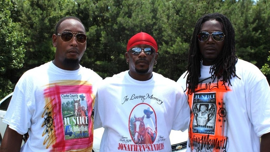 Friends of Jonathan Sanders poses for a photo with at his funeral service wearing T-shirts that honored Sanders and his love of horses Saturday, July 18, 2015, in Quitman, Miss. Sanders, who had been driving a horse and buggy died after a fight with a Stonewall police officer. (Jeff Byrd/The Meridan Star via AP) MANDATORY CREDIT