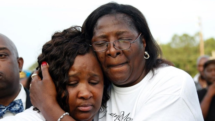 Frances Sanders, mother of Jonathan Sanders, right, hugs his sister Nicole Holloway, during a remembrance and rally for Jonathan Sanders in Stonewall, Miss., Sunday, July 19, 2015. Sanders died after a physical encounter with a white police officer on July 8, and had been riding in a two-wheeled buggy pulled by a horse. (AP Photo/Rogelio V. Solis)