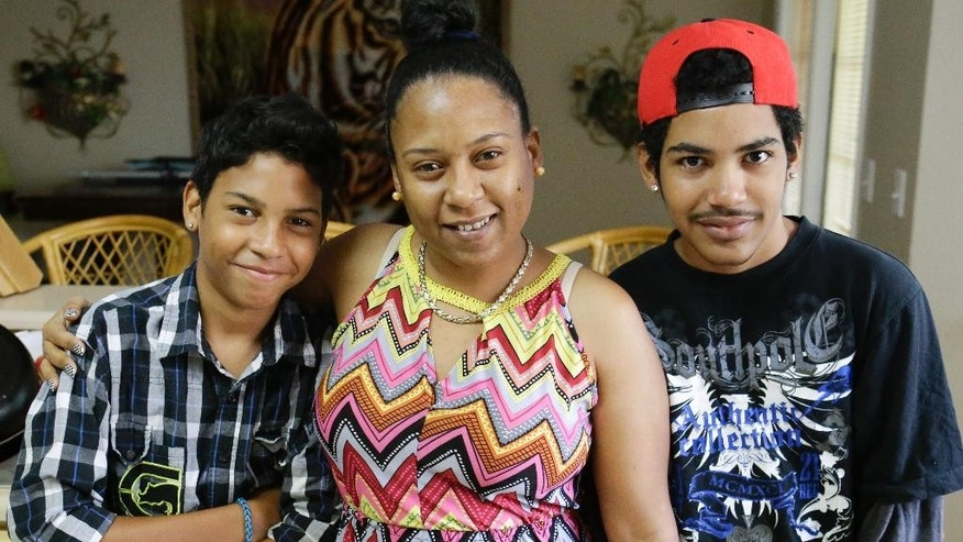 In this Thursday, July 16, 2015 photo, Mayra Rios, center, poses for a photo with her sons, Abdiel, 13, left, and Jonatan, 15, at their home in Orlando, Fla. Rios recently left her native Puerto Rico because of constant bullying her autistic son faced at school and the lack of services available for him. As Puerto Rico struggles with an unpayable debt, an unemployment rate over 12 percent, rising violence and a stagnant economy that offers little opportunity to thrive, thousands of its residents are abandoning the island for central Florida. (AP Photo/John Raoux)