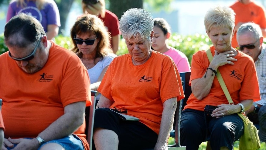 Rodney Gray, left, prays during a memorial service at River Park Saturday, July 18, 2015, in Chattanooga, Tenn., for the victims of the Tennessee shootings. Muhammad Youssef Abdulazeez, of Hixson, Tenn., attacked two military facilities on Thursday, in a shooting rampage that killed four Marines and one U.S. Navy sailor. (AP Photo/Mark Zaleski)