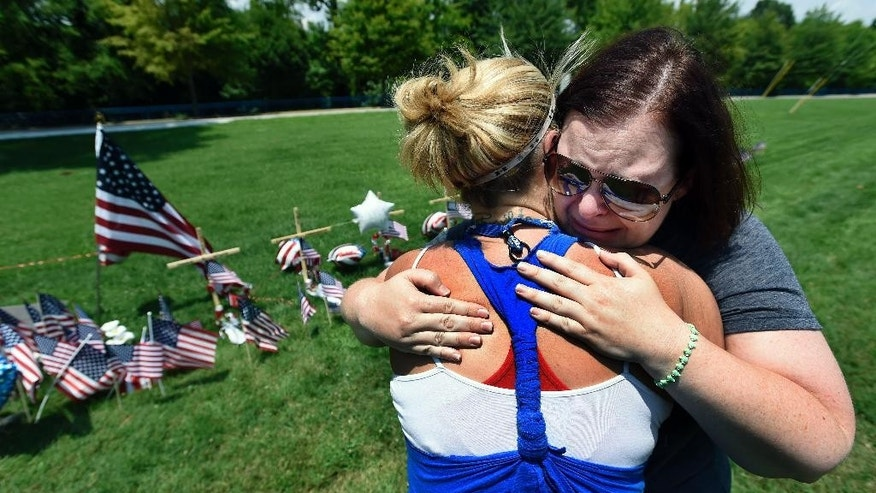 Sophia Ensley, left, comforts Barbie Branum by a makeshift memorial at the entrance to the Naval Operational Support Center and Marine Reserve Center Saturday, July 18, 2015, in Chattanooga, Tenn. The U.S. Navy says a sailor who was shot in the attack on a military facility in Chattanooga has died, raising the death toll to five people. (AP Photo/Mark Zaleski)