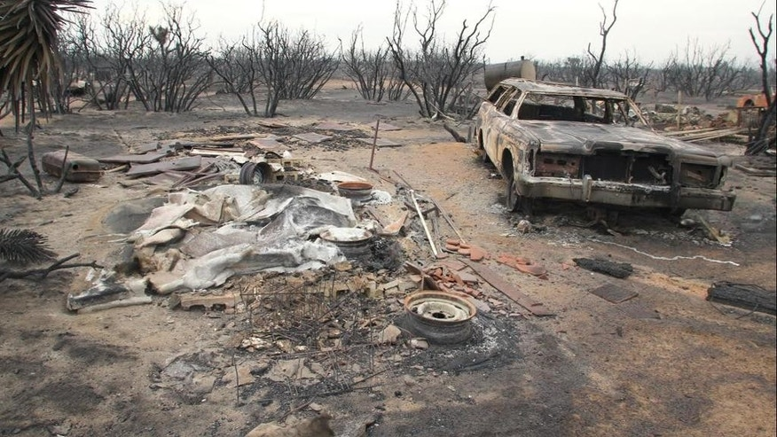 A burned-out car is seen on Saturday, July 18, 2015, in the rural community of Baldy Mesa, Calif. A wildfire swept across Interstate 15 on Friday, destroying over a dozen vehicles before burning several homes in the community of Baldy Mesa. (AP Photo/Matt Hartman)