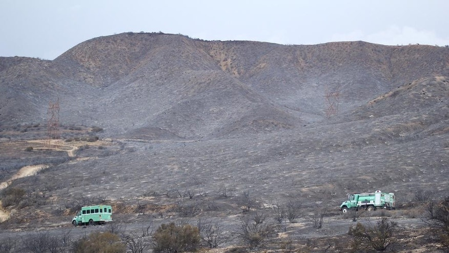 California Department of Forestry and Fire Protection trucks drive past burned terrain next to the southbound side of Interstate 15, the main connector between Southern California and Las Vegas in the Cajon Pass, Calif., on Saturday, July 18, 2015. The fire swept across Interstate 15 on Friday, destroying the vehicles before burning three homes and 44 more vehicles in the community of Baldy Mesa. It has blackened 5.5 square miles. (AP Photo/Matt Hartman)