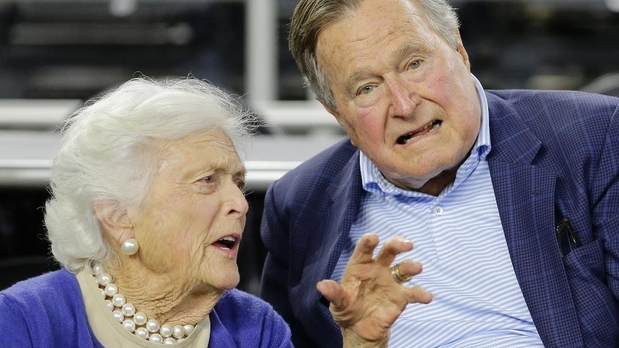 FILE- In this March 29, 2015, file photo, former President George H.W. Bush and his wife Barbara Bush speak before the first half of an NCAAA college basketball game in Houston. A spokesman says doctors are pleased with the progress the former president is making since he fractured a bone in his neck during a fall. Jim McGrath said Sunday, July 19, 2015, that Bush is doing better and his spirits are good. (AP Photo/David J. Phillip, File)