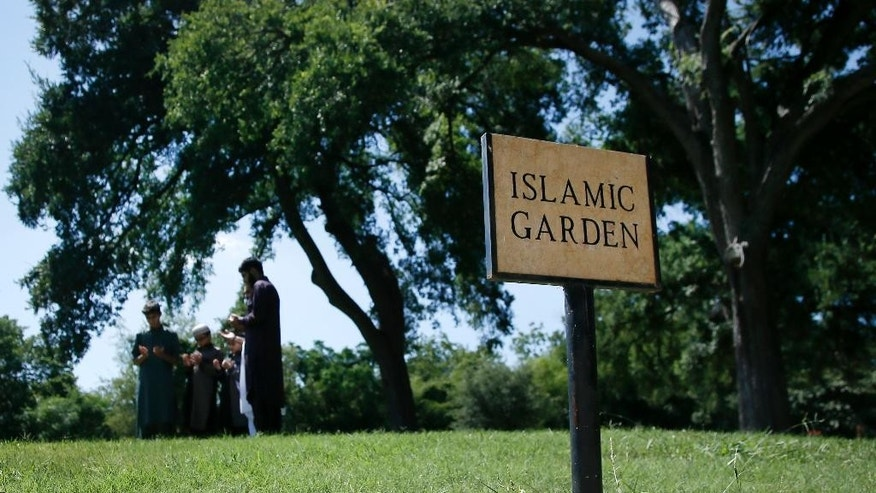A family gathers in prayer as they visit a family member buried in the Islamic Garden at Restland Cemetery  Friday, July 17, 2015, in Dallas. A proposal to bring a Muslim cemetery to Farmersville has stoked fears among residents who are vehemently trying to convince community leaders to block the project. (AP Photo/Tony Gutierrez)