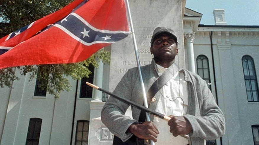 Anthony Hervey holds a Confederate flag while standing underneath the Confederate monument in Oxford, Miss in 2000.
