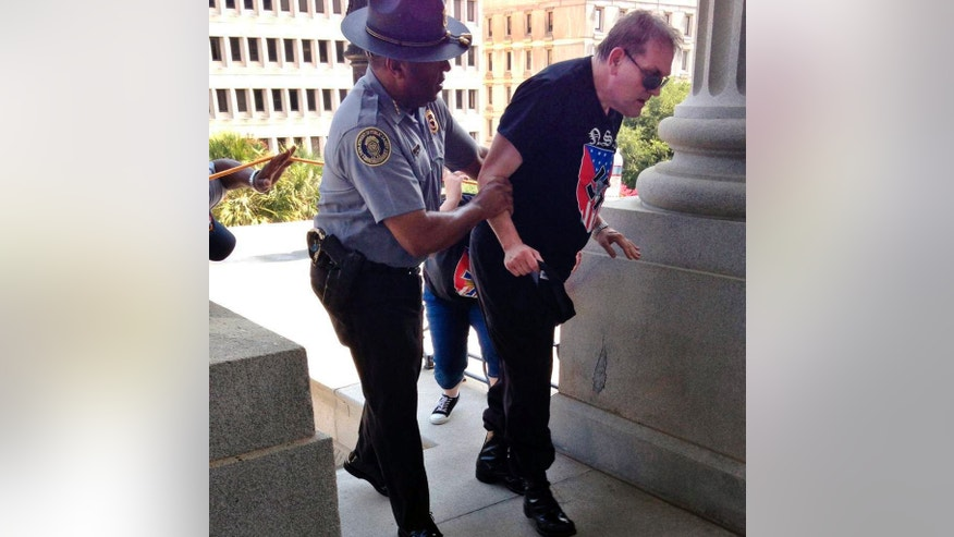 FILE - In this July 18, 2015 photo provided by Rob Godfrey, police officer Leroy Smith, left, helps a man wearing National Socialist Movement attire up the stairs during a rally in Columbia, S.C. Smith, the director of South Carolina's public safety agency, said Monday, July 20, 2015, he hopes the photo that shows him helping the white man wearing a racist T-shirt will be a catalyst for people to work toward overcoming hate and violence. (Rob Godfrey via AP, file)