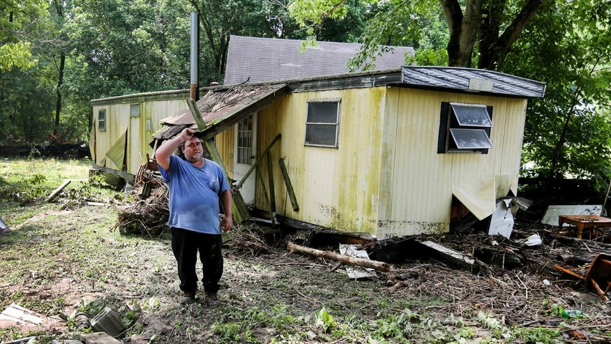 Sunday, July 19, 2015: Jeff Downing, walks around his property in Ripley, Ohio. Downing's mobile home had previously been in the foreground where the bricks are prior to a late evening flash flood.