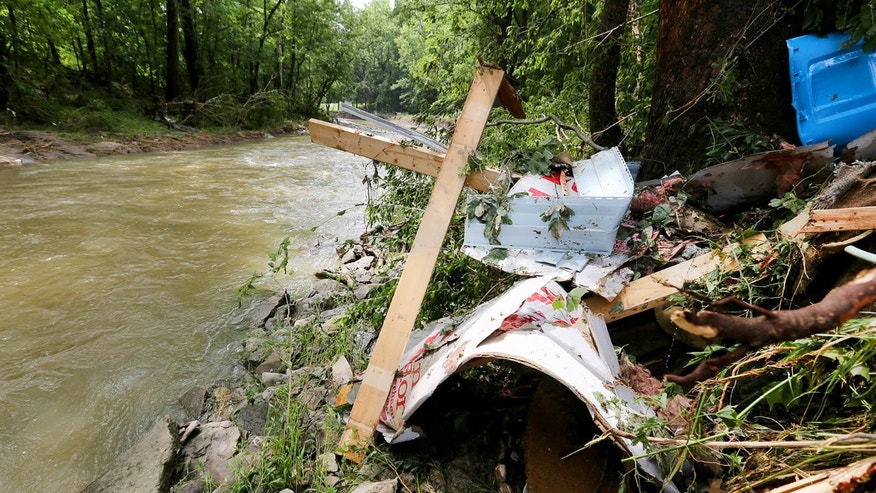 Sunday, July 19, 2015:  Debris rests on the bank of Red Oak Creek where a mobile home was swept off its foundation in Ripley, Ohio.