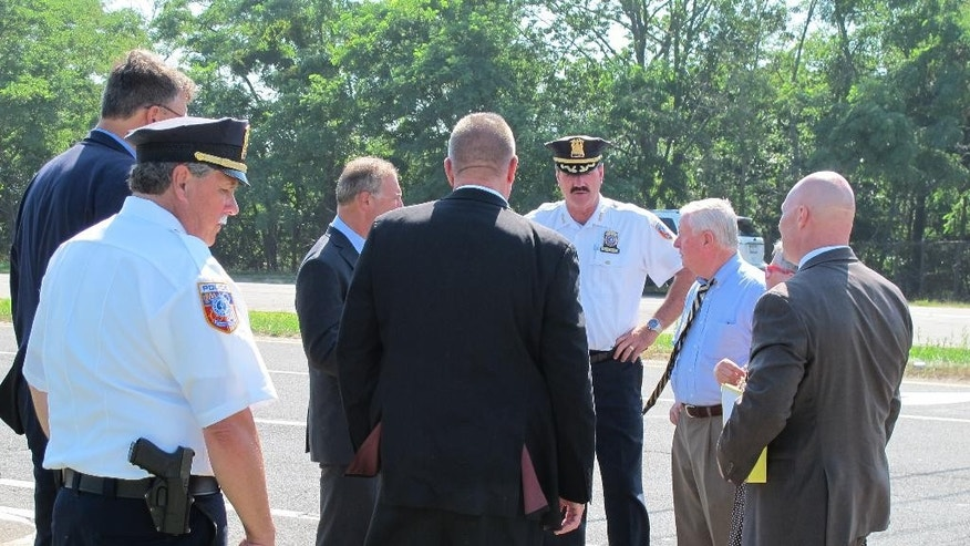 Suffolk County District Attorney Thomas Spota, third from right wearing a tie, speaks with investigators, Monday, July 20, 2015, in Cutchogue, N.Y., following a crash where four young women riding in a limousine were killed in a car accident on Saturday. Police have charged the driver of a pickup truck that slammed into the limousine with driving while intoxicated. (AP Photo/Frank Eltman)