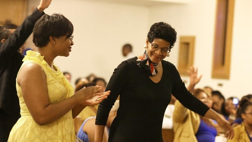 Geneva Read-Veal, right, and her daughter Sharon Cooper react to a prayer during a memorial service for her other daughter Sandra Bland at Prairie View A&M University, Tuesday, July 21, 2015, in Prairie View, Texas. A newly released dashcam video documents how a routine traffic stop escalated into a shouting confrontation between a Texas state trooper and Bland, which led to her arrest. Bland was found hanging in her jail cell three days after the incident. (AP Photo/Pat Sullivan)