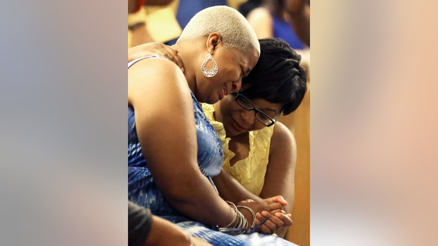 Shante Needham, left, and Sharon Cooper comfort one another at a memorial service for their sister Sandra Bland at Prairie View A&M University, Tuesday, July 21, 2015, in Prairie View, Texas. A newly released dashcam video documents how a routine traffic stop escalated into a shouting confrontation between a Texas state trooper and Bland, which led to her arrest. Bland was found hanging in her jail cell three days after the incident. (AP Photo/Pat Sullivan)