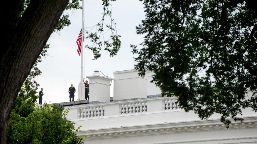 The American flag is lowered to half staff above the White House in Washington, Tuesday, July 21, 2015, to honor the five U.S. service members who were killed by a gunman in Chattanooga, Tenn. last week. President Obama has ordered flags at all military and federal buildings and grounds through out the United States to remain at half-staff through July 25th. (AP Photo/Andrew Harnik)