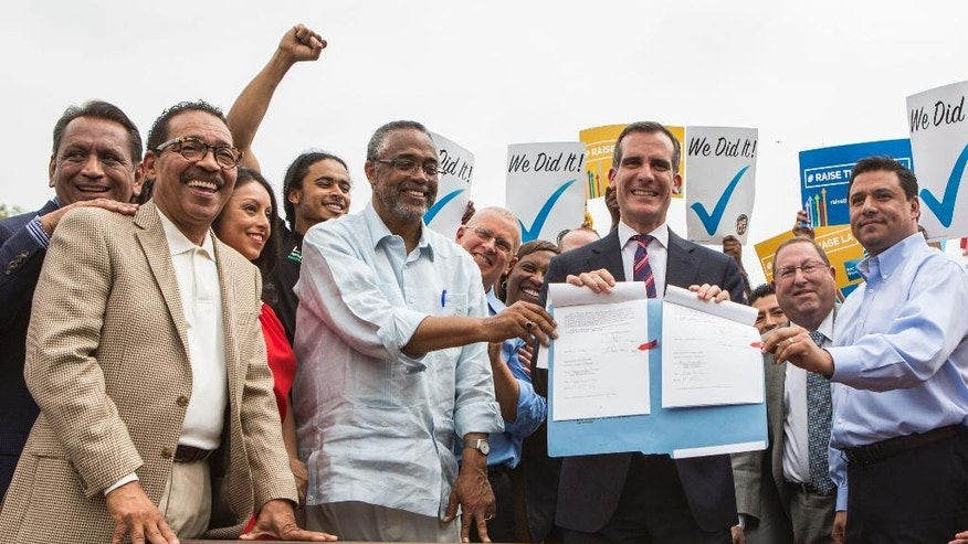 FILE - In this Saturday, June 13, 2015 file photo, Los Angeles Mayor Eric Garcetti, center right, joins members of the City Council and community leaders in a photo after he signed into law an ordinance that will gradually raise the minimum wage to $15 an hour by 2020 in Los Angeles. The Los Angeles County Board of Supervisors is expected to take a preliminary step Tuesday, July 21, 2015, that could lead to the higher wages. (AP Photo/Ringo H.W. Chiu, File)