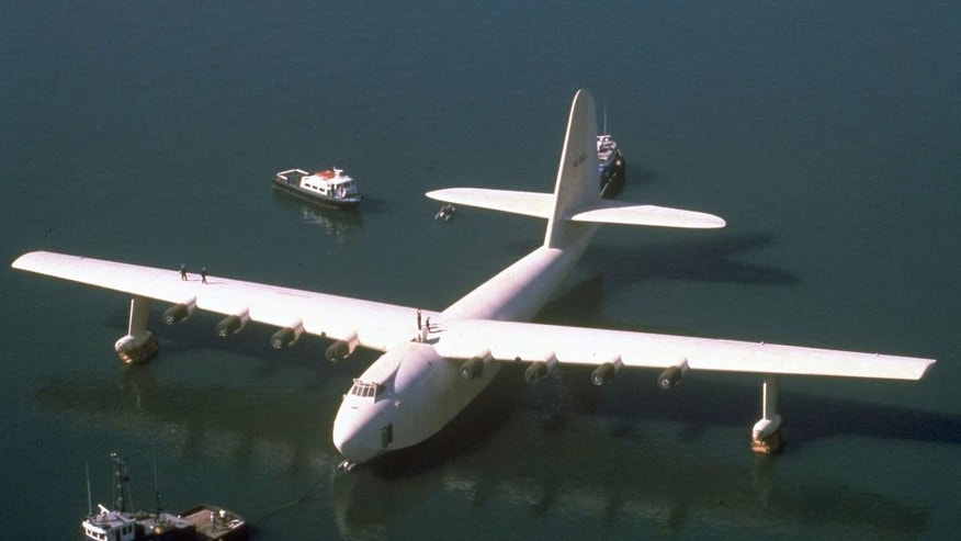 "FILE - In this Oct. 29, 1980 file photo, Howard Hughes' wooden flying boat the ""Spruce Goose,"" is towed by a tugboat from its hangar in Long Beach, Calif. The gigantic historic wooden airplane whose fate was mired in a financial dispute, will permanently stay in Oregon. The Evergreen Aviation and Space Museum has reached an agreement with the Aero Club of Southern California to take full ownership of the plane in the coming weeks, said California attorney Robert E. Lyon, who represents the Aero Club. Lyon said the agreement was reached in early July 2015. (AP Photo, File)"