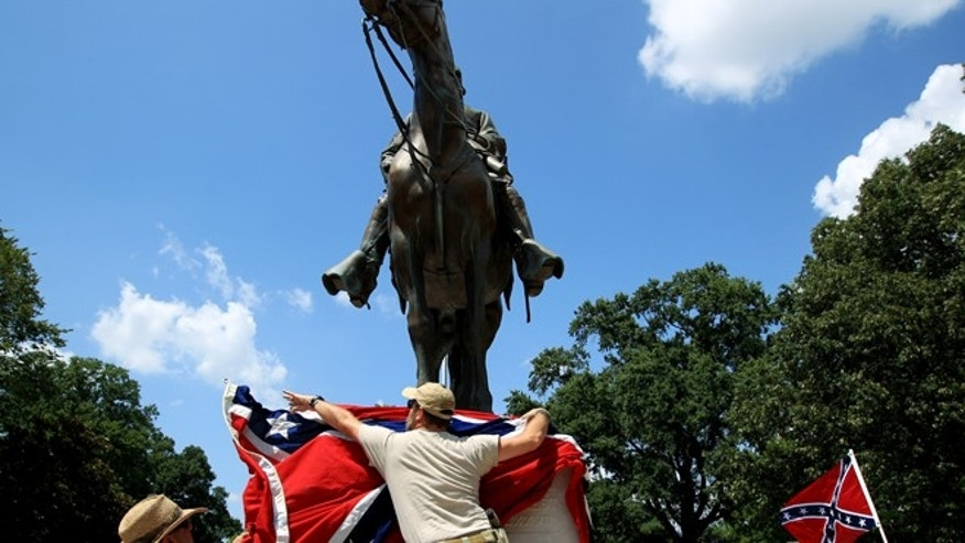 Mike Goza, left, helps Mike Junor drape a Confederate flag over the base of the statue and tomb of Nathan Bedford Forrest, rebel general, slave trader and early Ku Klux Klan member, during a celebration of Forrest's 194th birthday at Health Sciences Park in Memphis, Tenn.