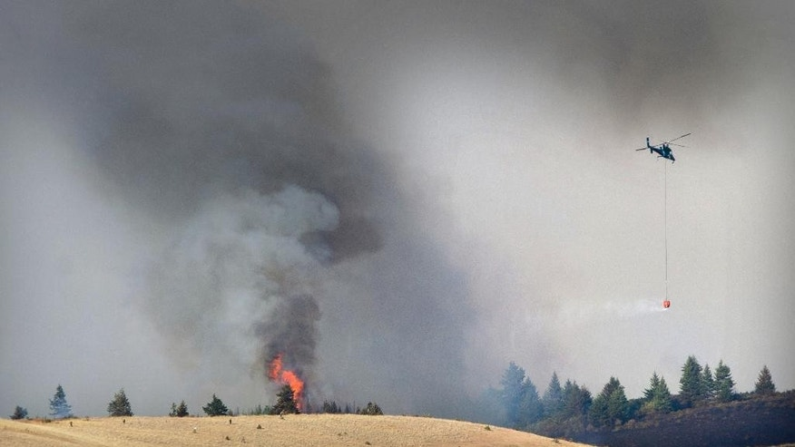 A helicopter flies by as a flame flares up along the western edge of the Blue Creek fire  in the Blue Mountains near Walla Walla,  Wash., on Monday, July 20, 2015.  Several wildfires lit up Washington state on Tuesday, closing freeways, including a major east-west artery, destroying at least one home and threatening dozens of others. (Greg Lehman/Walla Walla Union-Bulletin via AP)  MANDATORY CREDIT