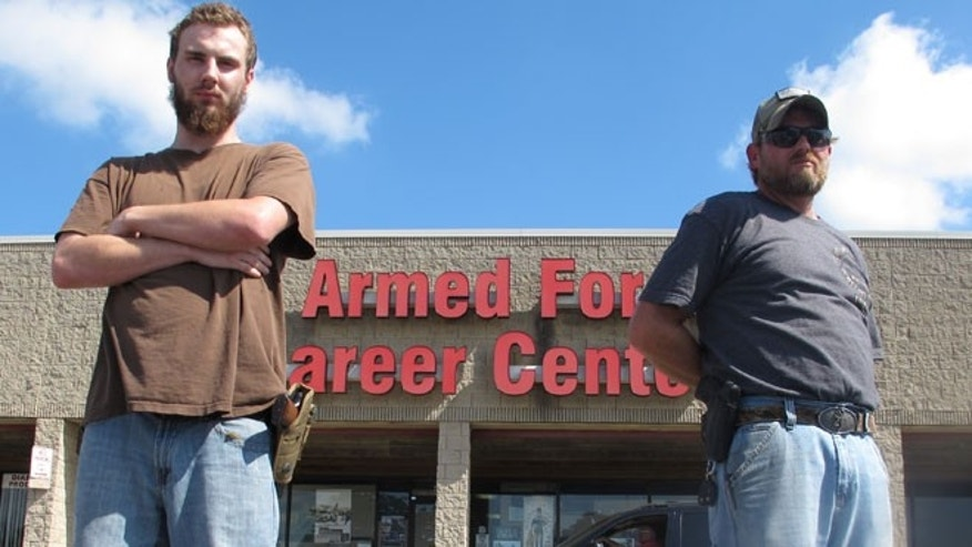 Allen Bowles, left, and Clint Janney stand guard outside a military recruiting center in Columbus, Ohio.