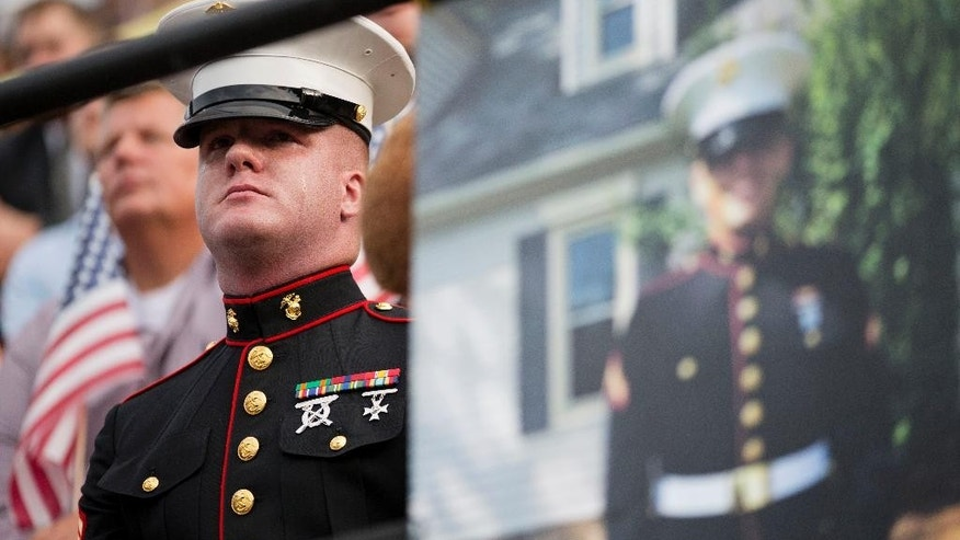 "A tear rolls down the cheek of Sgt. Benjamin Tranter, a former classmate of Lance Cpl. Squire Wells, known as ""Skip,"" seen in photo at right, as he attends a memorial service for Wells at Sprayberry High School where they both attended, Tuesday, July 21, 2015, in Marietta, Ga. Crowds gathered at the suburban Atlanta high school to remember the Marine who was fatally shot in an attack on military facilities in Chattanooga, Tenn. (AP Photo/David Goldman)"