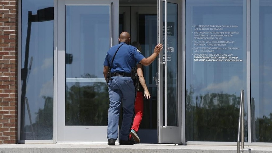 A sheriff's deputy enters the Arapahoe County District Court, where the trial of convicted Aurora movie theater shooter James Holmes continued Wednesday, July 22, 2015, in Centennial, Colo. The monthlong penalty phase of the trial of Holmes, who could be sentenced to death for killing 12 people in a Colorado movie theater, began Wednesday morning with the judge giving instructions to the jury. (AP Photo/Brennan Linsley)