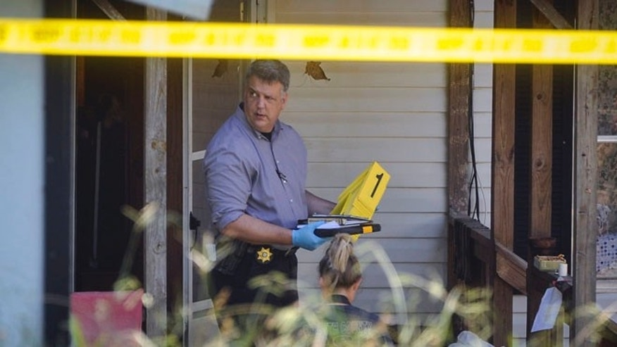 Law enforcement officials investigate the scene of a shooting at a home in Suwanee, Ga.
