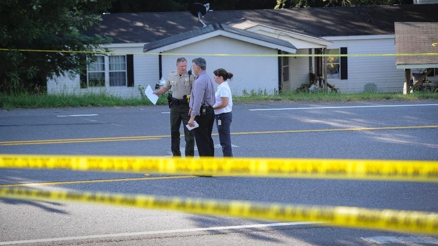 Law enforcement investigate the scene of a shooting at a home in Suwanee, Ga., Wednesday, July 22, 2015, where a gunman killed a woman and two children and wounded another man before killing himself inside the suburban Atlanta home, according to Forsyth County Sheriff Duane Piper. (AP Photo/John Amis)