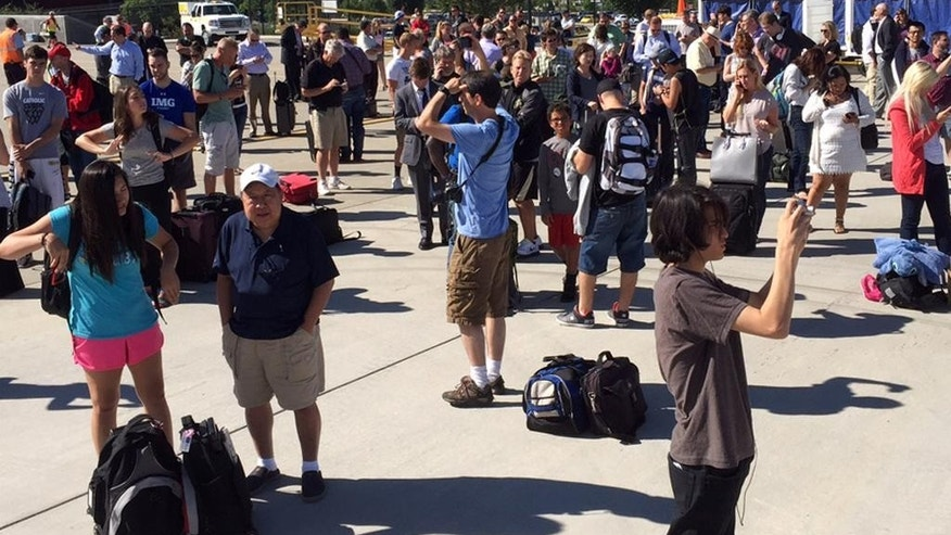 In this photo provided by Jeremy Kissinger passengers being evacuated from United Airlines Flight 447 gather at the Grand Junction Regional Airport on Wednesday, July 22, 2015, in Grand Junction, Colo. The flight from Denver to Los Angeles was diverted to Grand Junction after a number of passengers reported feeling ill. (Jeremy Kissinger via AP)