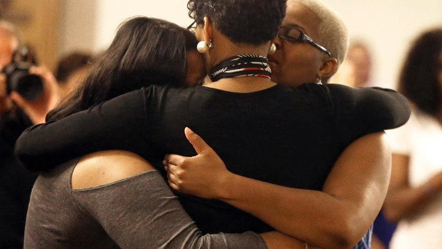 CORRECTS SPELLING OF LAST NAME TO REED-VEAL, NOT READ-VEAL - Geneva Reed-Veal, center, hugs family members at a memorial service for her daughter Sandra Bland at Prairie View A&M University, Tuesday, July 21, 2015, in Prairie View, Texas. A newly released dashcam video documents how a routine traffic stop escalated into a shouting confrontation between a Texas state trooper and Bland, which led to her arrest. Bland was found hanging in her jail cell three days after the incident. (AP Photo/Pat Sullivan)