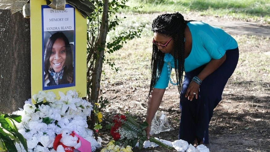 Jeanette Williams places a bouquet of roses at a memorial for Sandra Bland near Prairie View A&M University, Tuesday, July 21, 2015, in Prairie View, Texas. A newly released dashcam video documents how a routine traffic stop escalated into a shouting confrontation between a Texas state trooper and Bland, which led to her arrest. Bland was found hanging in her jail cell three days after the incident. (AP Photo/Pat Sullivan)