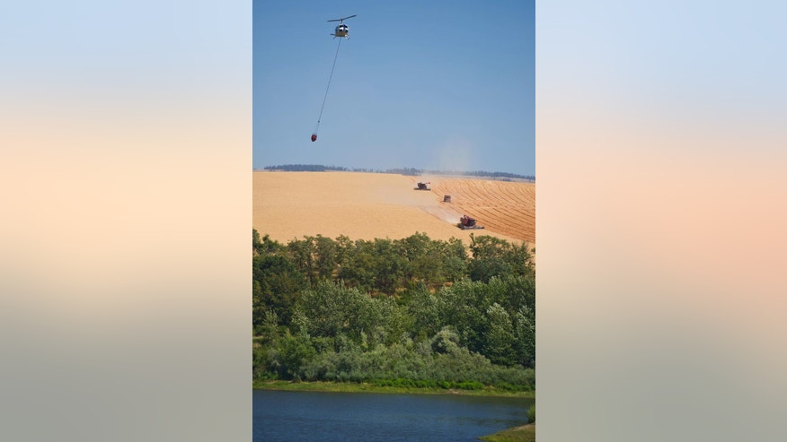 A firefighting helicopter arrives to dip water from Bennington Lake east of Walla Walla, Wash., Tuesday afternoon, July 21, 2015. Walla Walla County Commissioners have declared a state of emergency due to a wildfire that's destroyed one home and was threatening dozens of others. (Greg Lehman/Walla Walla Union-Bulletin via AP)
