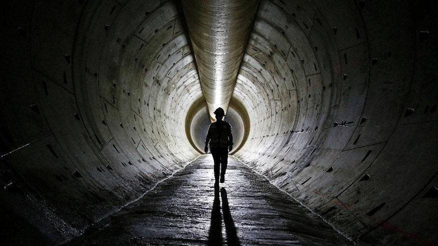 FILE - In this June 1, 2015, file photo, Robin Rockey, of the Southern Nevada Water Authority, walks through a tunnel still under construction beneath Lake Mead near Boulder City, Nev. The Conference Board reports on its index of leading economic indicators for June on Thursday, July 23, 2015. (AP Photo/John Locher, File)