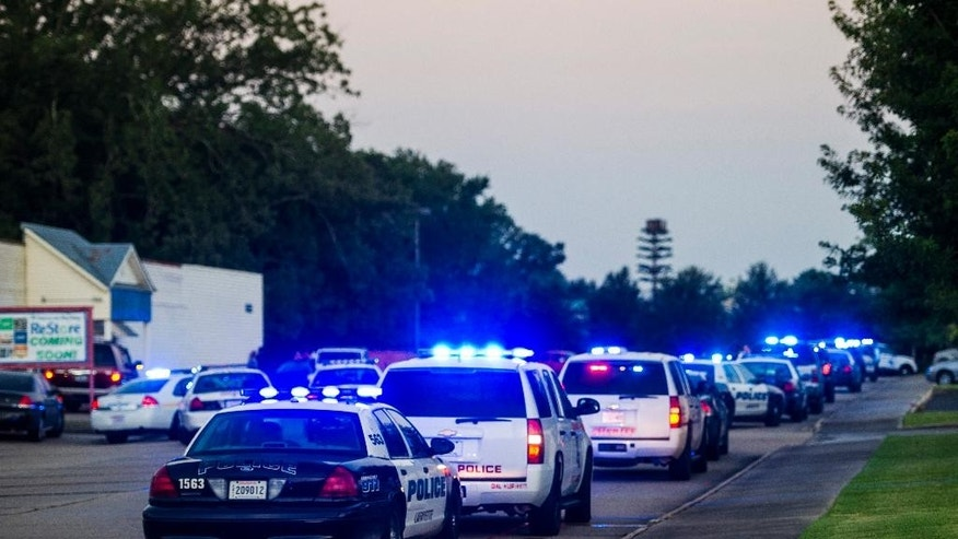 Lafayette Police Department and Louisiana State Police units block an entrance road following a shooting at The Grand Theatre in Lafayette, La., Thursday, July 23, 2015. (Paul Kieu/The Daily Advertiser via AP)