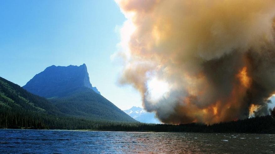 In this photo provided by Erin Conwell, taken Tuesday, July 21, 2015, smoke from the Reynolds Creek wildfire rises above the landscape at St. Mary Lake in Glacier National Park, Mont. The fire burning in the drought-parched northwestern Montana park doubled in size Wednesday, leading officials to evacuate homes along St. Mary Lake and visitors to flee hotels and campgrounds in the nearby community at Glacier's eastern entrance. (Erin Conwell via AP)