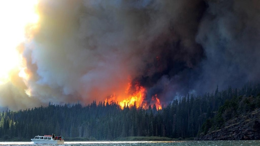 In this photo provided by Erin Conwell, taken Tuesday, July 21, 2015, fire and smoke from the the Reynolds Creek wildfire rises above the landscape at St. Mary Lake in Glacier National Park, Mont. The fire burning in the drought-parched northwestern Montana park doubled in size Wednesday, leading  officials to evacuate homes along St. Mary Lake and visitors to flee hotels and campgrounds in the nearby community at Glacier's eastern entrance. (Erin Conwell via AP)