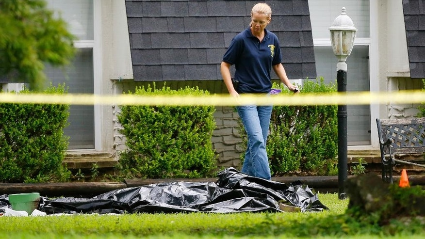 An investigator walks in the front yard of a house in Broken Arrow, Okla., Thursday, July 23, 2015, where five family members were discovered stabbed to death. Two teenagers were taken into custody. (AP Photo/Sue Ogrocki)