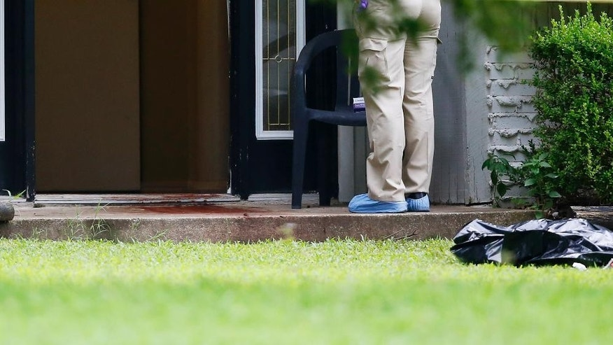 A quantity of blood can be seen on the doorstep of a house in Broken Arrow, Okla., Thursday, July 23, 2015, where five family members were discovered stabbed to death. Two teenagers were taken into custody. (AP Photo/Sue Ogrocki)