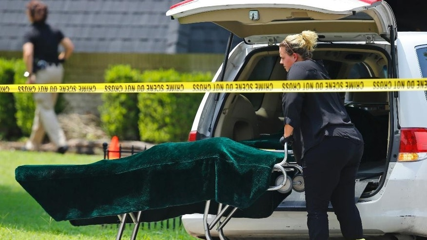A worker wheels a gurney with a body bag on it, under the green cover, to a coroner's van outside of a home in Broken Arrow, Okla., Thursday, July 23, 2015, where five family members were discovered stabbed to death. Two male teenagers are in custody. Police say they and the victims are related. (AP Photo/Sue Ogrocki)