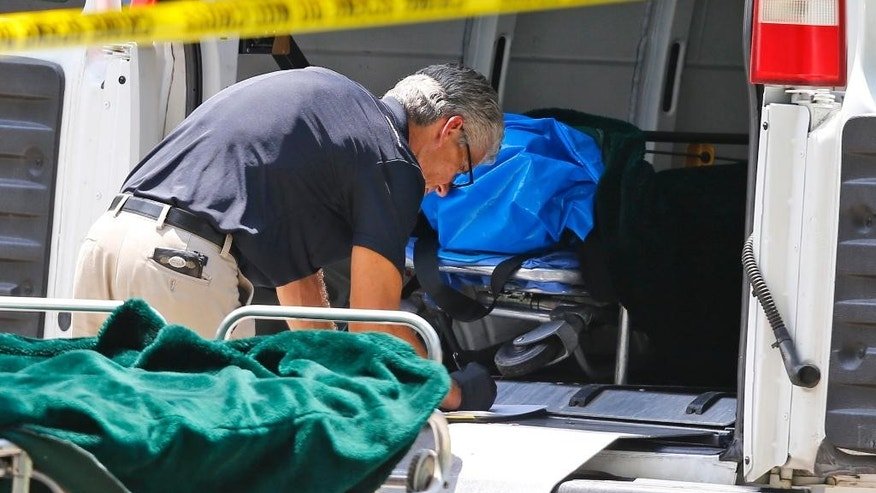 A worker does paperwork near a gurney with a body bag on it in the door of a coroner's van outside of a home in Broken Arrow, Okla., Thursday, July 23, 2015, where five family members were discovered stabbed to death. (AP Photo/Sue Ogrocki)