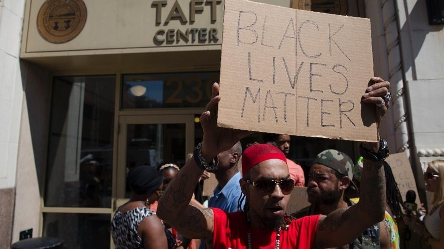 Anthony Lattimore holds a sign outside the office of Hamilton County prosecutor Joe Deters' office during a protest demanding release of video showing the shooting death of Samuel Dubose by a University of Cincinnati police officer, Thursday, July 23, 2015, in Cincinnati. Deters has said he won't release the video until the investigation into Sunday's shooting is complete. (AP Photo/John Minchillo)