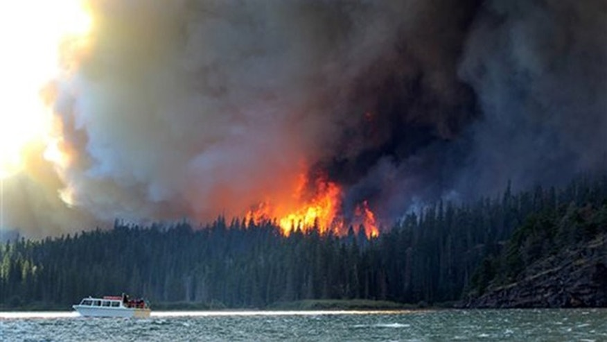 In this photo provided by Erin Conwell, taken Tuesday, July 21, 2015, fire and smoke from the the Reynolds Creek wildfire rises above the landscape at St. Mary Lake in Glacier National Park, Mont.