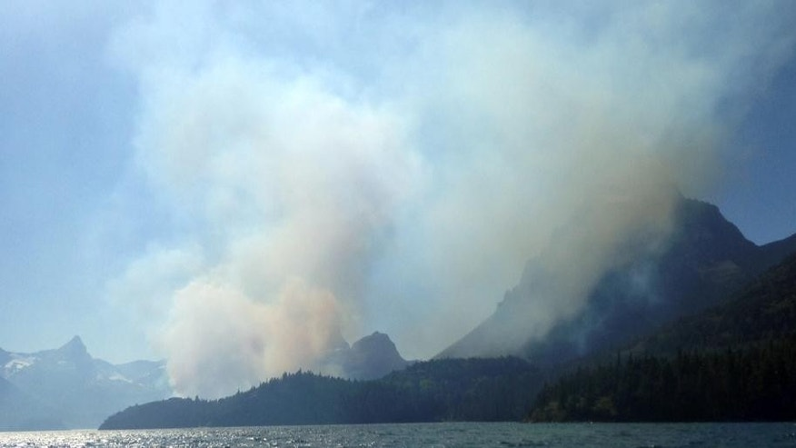 In this photo taken Tuesday, July 21, 2015, smoke from the the Reynolds Creek wildefire rises above the landscape at St. Mary Lake in Glacier National Park, Mont. The fast-moving wildfire torched a car and forced tourists to abandon their vehicles on the Montana park's most popular roadway while officials evacuated hotels, campgrounds and homes. The National Weather Service warned that wind gusts combined with low humidity in the park and the rest of northwestern Montana had created extreme conditions for wildfires Wednesday afternoon. (Erin Conwell via AP)